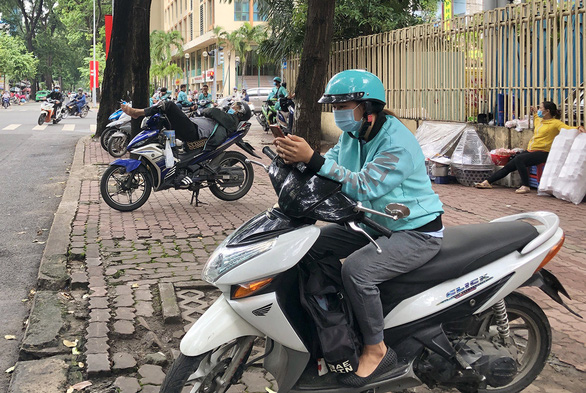 Tran Thi Thu Ngan, 21, is spotted waiting opposite a bubble milk tea shop in Ho Chi Minh City, Vietnam for new orders on her phone. Photo: Dieu Qui/ Tuoi Tre