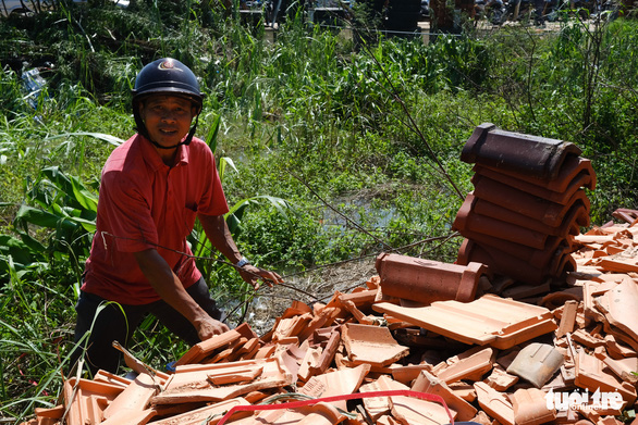 Le Quang Nghia collects fragmented but usable tiles abandoned by stores to fix his roof after Storm Molave in Quang Ngai Province, October 29, 2020. Photo: Tan Luc / Tuoi Tre