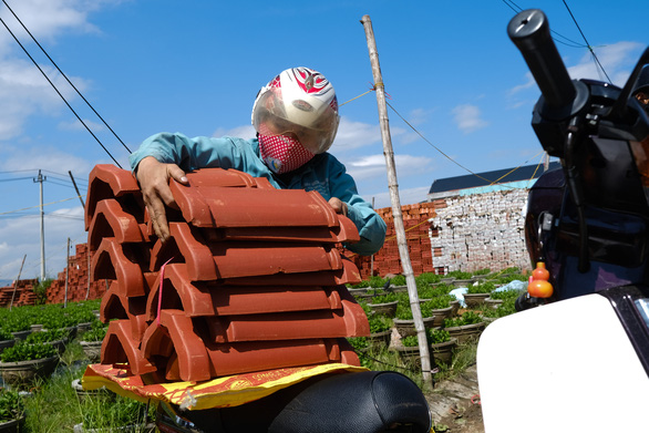 Pham Thi Phuong put tiles she has just purchased on her motorbike in Quang Ngai Province, October 29, 2020. Photo: Tan Luc / Tuoi Tre