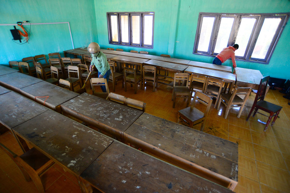 Teachers of Binh Chau Secondary School of Quang Ngai Province clean up a classroom after Typhoon Molave.
