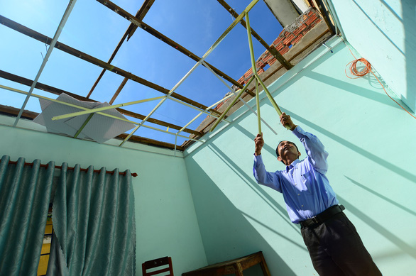 A teacher of Duc Thang Secondary School of Quang Ngai Province cleans up a classroom with roof blown away after Typhoon Molave