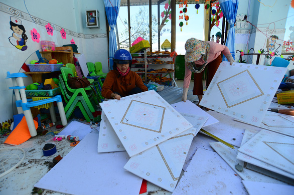 Teachers of Tinh Khe Kindergarten clean up roofing pieces after Typhoon Molave