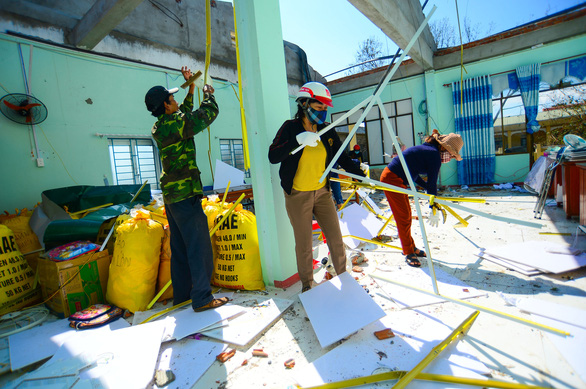 Parents are seen assisting teachers at Tinh Khe Kindergarten of Quang Ngai City to clean up the debris
