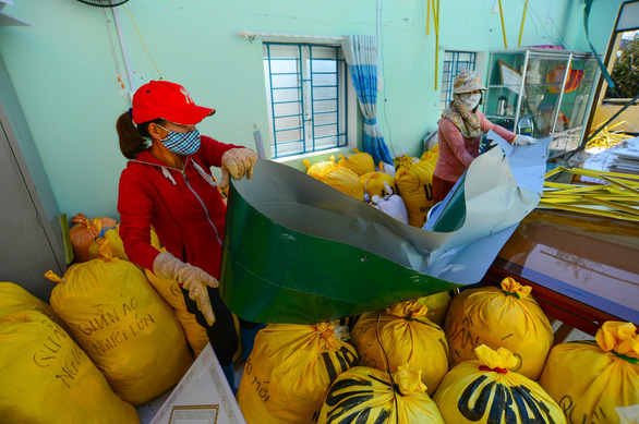 Teachers clean up debris in a room filled with bags of charity clothing intended for flooding victims in Quang Binh province