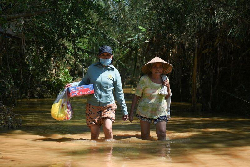 Women walk in a flooded road after their village was isolated by the Dakdrinh Hydropower discharge in the Typhoon Molave aftermath, in Tinh An village, Quang Ngai province, Vietnam October 29, 2020. Photo: Reuters