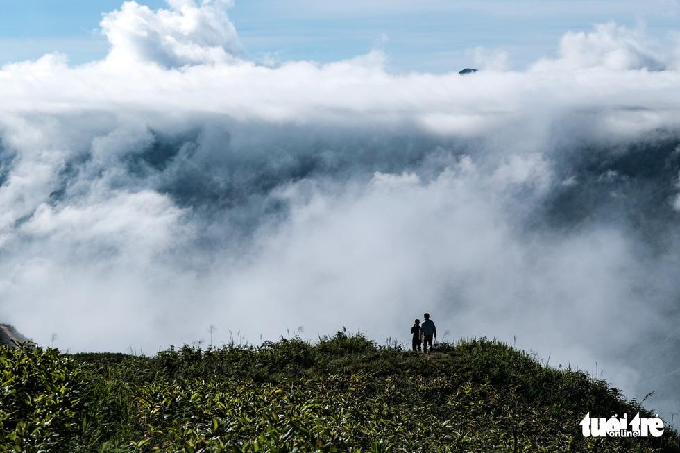 Tourists stop on a mountain trail to take photos at Hang Dong Commune, Bac Yen District, Son La Province, Vietnam. Photo: Nam Tran / Tuoi Tre