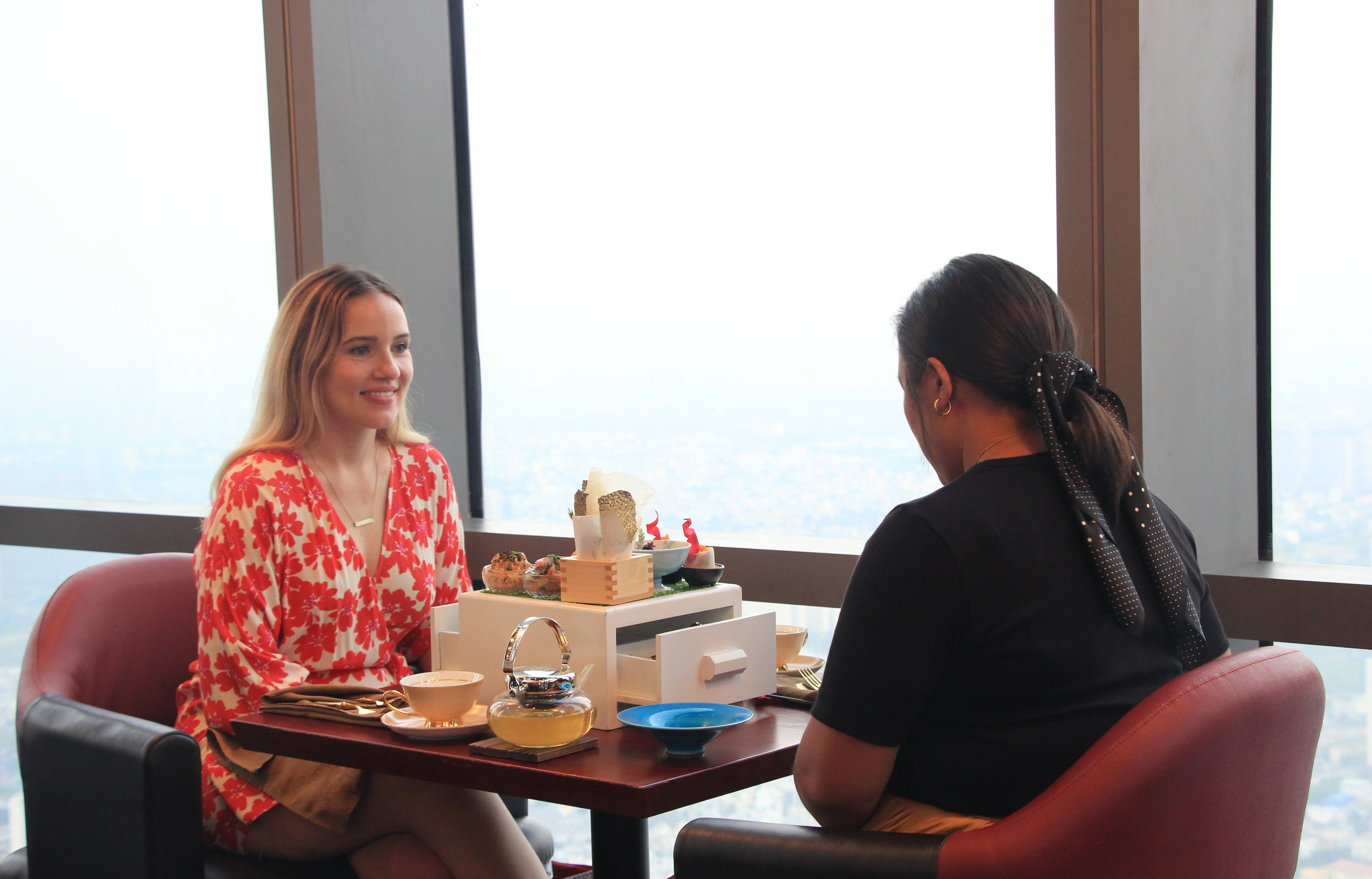 Canadian travel blogger Alyshia Turchyn talks with her friend Sam while enjoying the High Tea in the Sky afternoon tea set at Miwaku Premium Restaurant on the 80th floor at the 81-story Landmark 81 in Ho Chi Minh City's Binh Thanh District on October 22, 2020. Photo: Dong Nguyen/ Tuoi Tre News