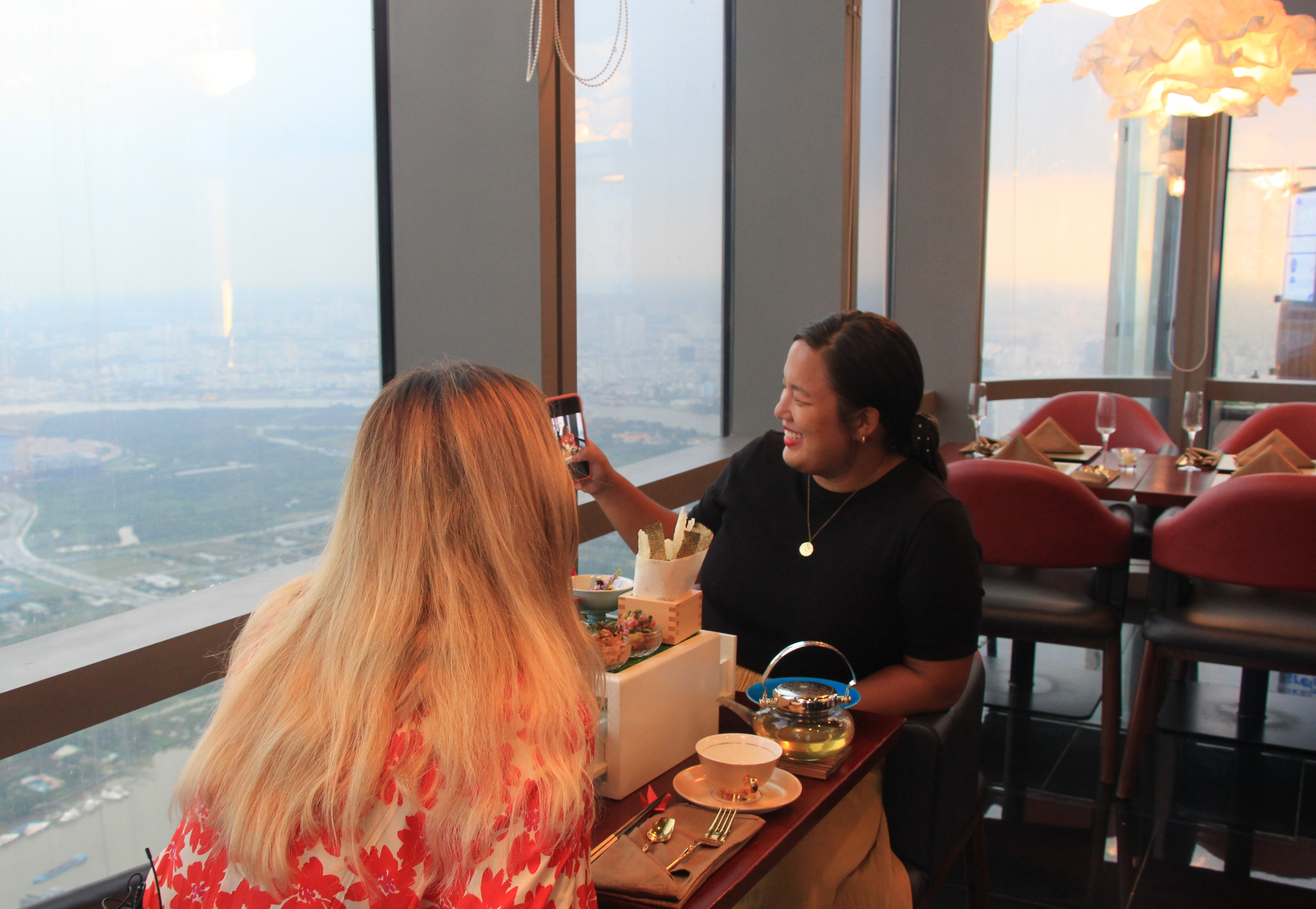 American travel blogger Samantha shows her friend a photo she has just taken while the two enjoying the High Tea in the Sky afternoon tea set at Miwaku Premium Restaurant on the 80th floor at the 81-story Landmark 81 in Ho Chi Minh City's Binh Thanh District on October 22, 2020. Photo: Dong Nguyen/ Tuoi Tre News