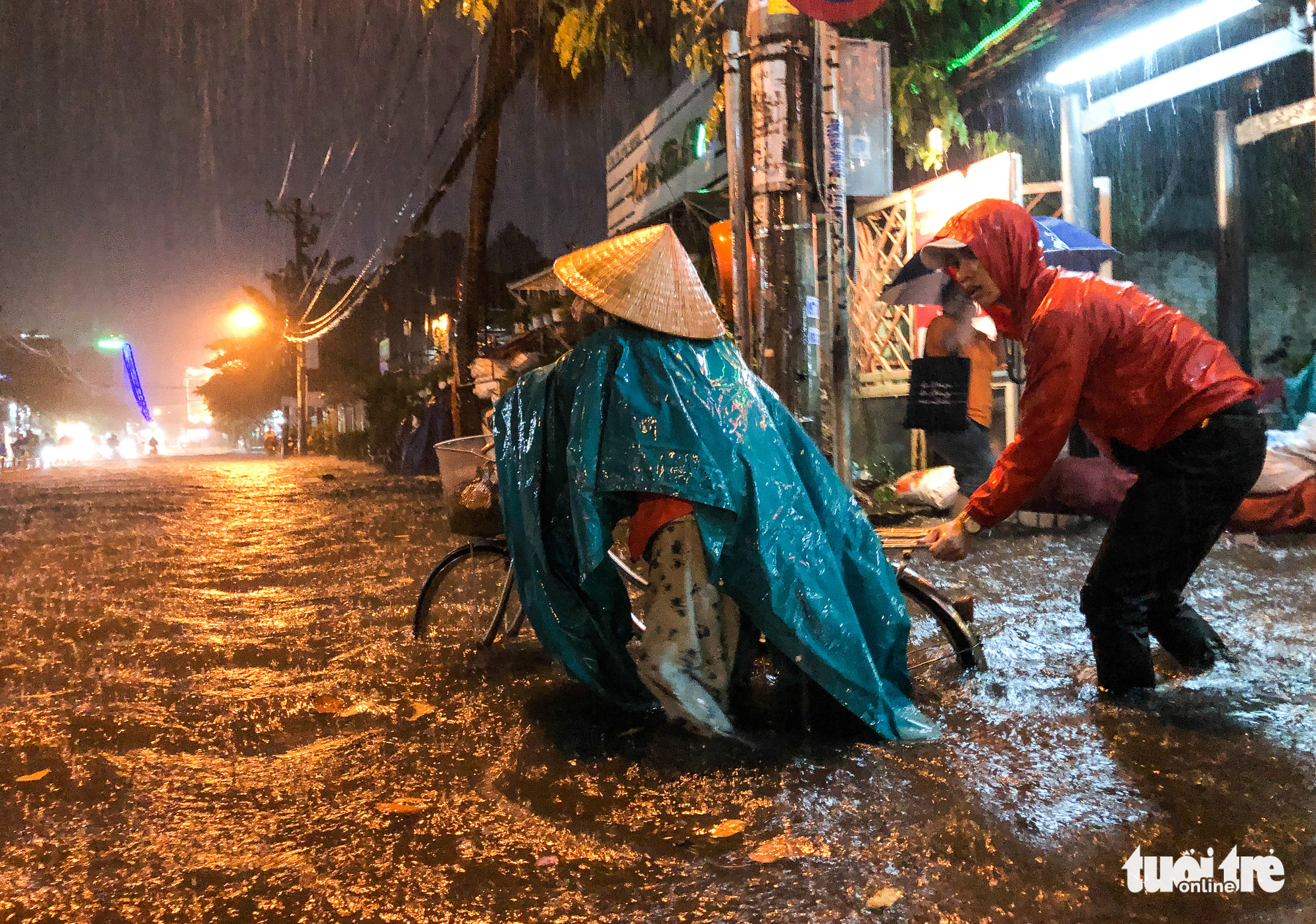 A man helps a cyclist on an inundated road in Ho Chi Minh City, October 31, 2020. Photo: Chau Tuan / Tuoi Tre