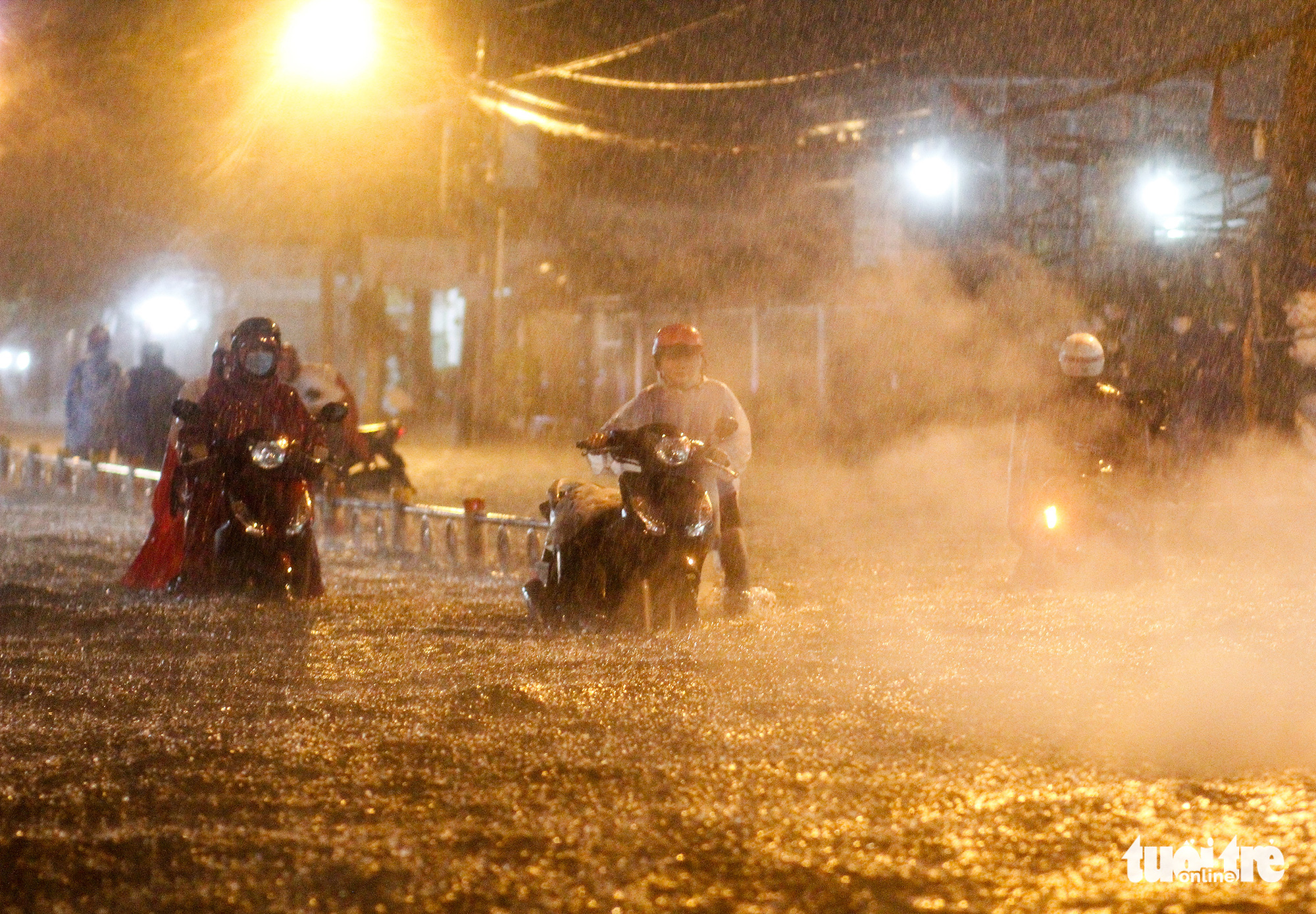 A woman pushes her broken-down motorbike on a flooded street in Ho Chi Minh City, October 31, 2020. Photo: Chau Tuan / Tuoi Tre