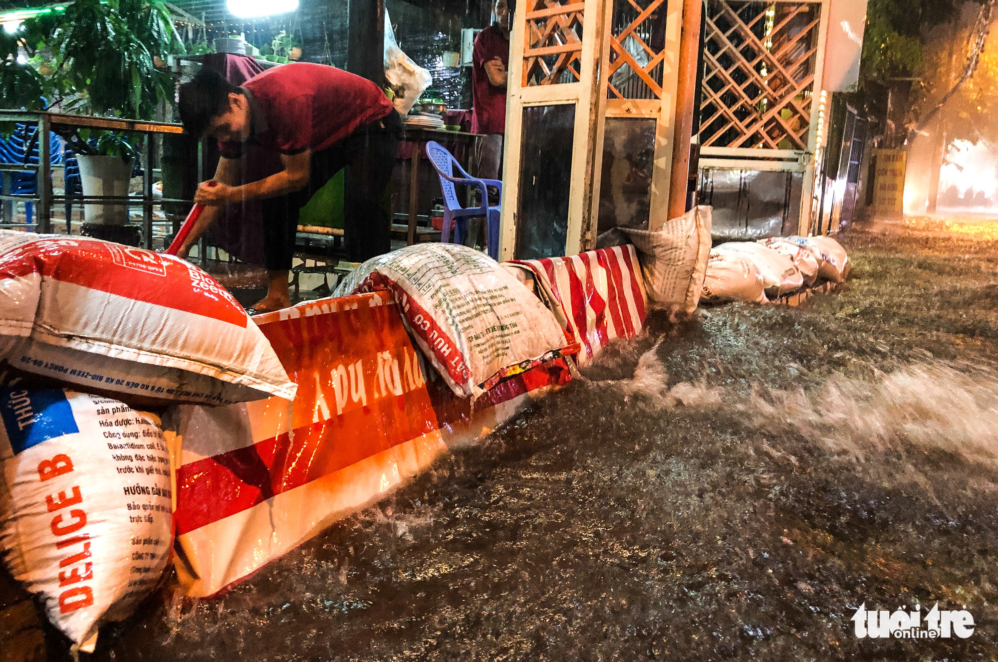 A man uses sandbags to prevent rainwater from pouring into his house in Ho Chi Minh City, October 31, 2020. Photo: Chau Tuan / Tuoi Tre