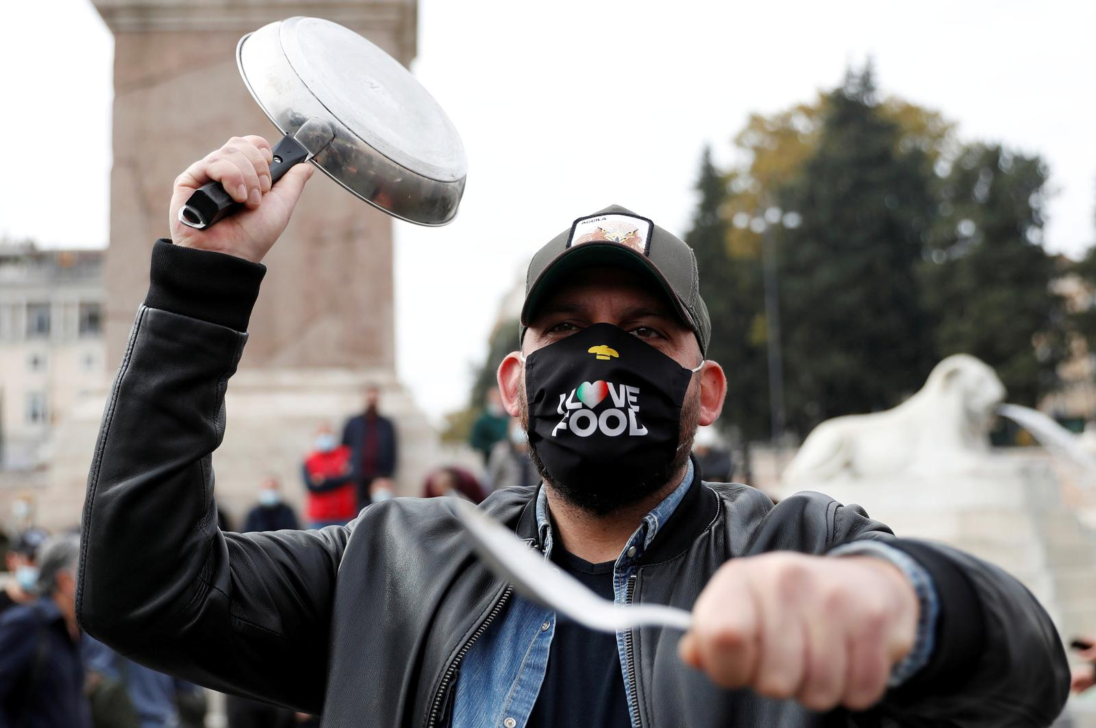 A man holds a frying pan as Italian restaurant and bar workers gather in Piazza del Popolo to protest against the government's coronavirus disease (COVID-19) rules that they have to close everyday by 6 p.m., in Rome, Italy November 2, 2020. Photo: Reuters