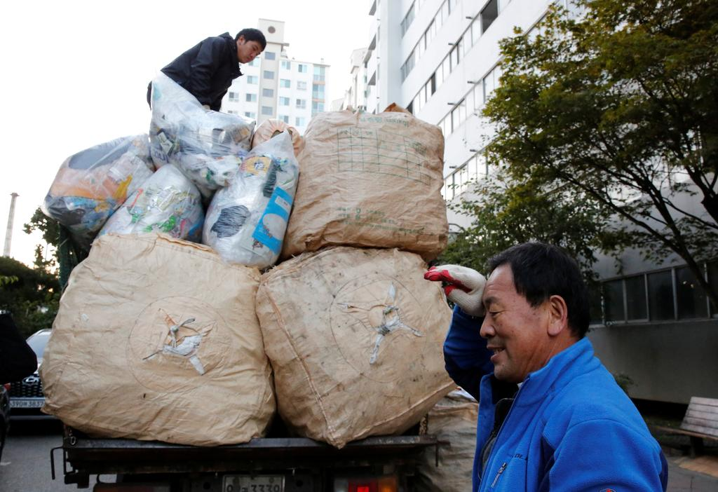 Lee Yong-gi, owner of a recycling facility, wipes sweat from his brow after collecting sacks of recycling garbage at an apartment area in Seoul, South Korea, October 23, 2020. Photo: Reuters
