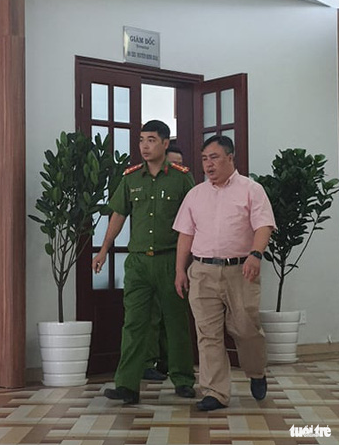 Nguyen Minh Khai, director of the Ho Chi Minh City Eye Hospital, leaves with a police officer following a working session on November 4, 2020. Photo: Huong Thao / Tuoi Tre