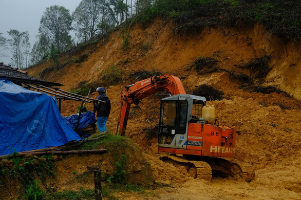 A vehicle is used to clear up mud from the landslide at Cua Village of Quang Ngai Province. Photo: Tran Mai / Tuoi Tre
