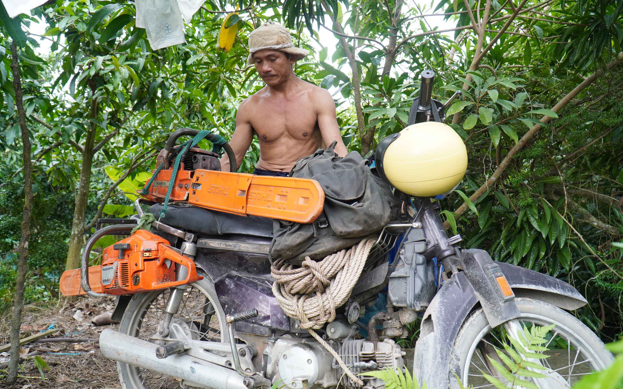 Pham Thanh Tung often travels on his motorbike packed with ropes and chainsaws in Tien Giang Province, Vietnam. Photo: Mau Truong / Tuoi Tre