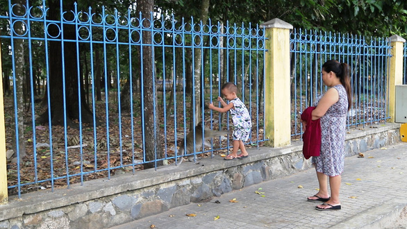 A child looks at a monkey from the other side of the fence in this photo taken in Tay Ninh Province. Photo: Tuan Anh / Tuoi Tre