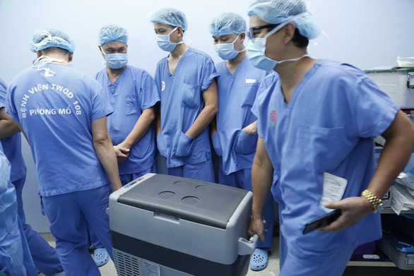 Medical practitioners at 108 Military Central Hospital carrying a box containing the heart of an organ donor in this supplied photo.