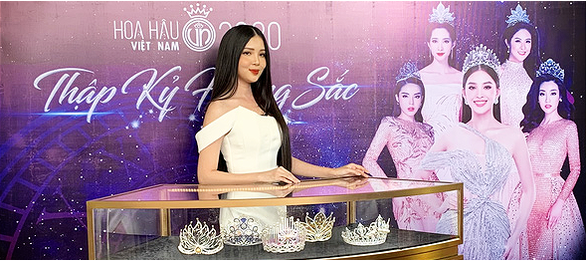 A beauty poses next to Miss Vietnam beauty pageant's crowns over the years.