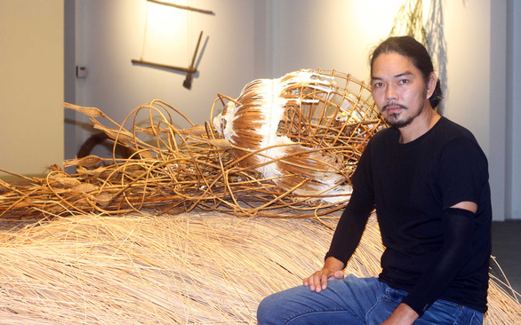 Artist Trung Nghia in front of one of his artworks at Hai An Gallery. Photo: Mai Thuy / Tuoi Tre
