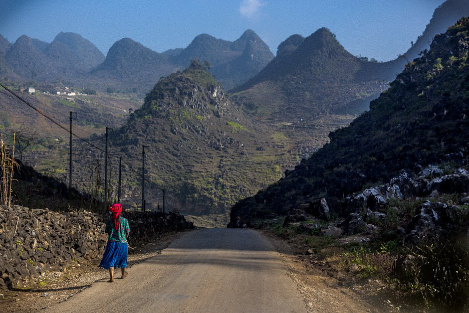 A walks on a road with mountains on the background in the northwest region of Vietnam captured in a photo by Thibault Clemenceau