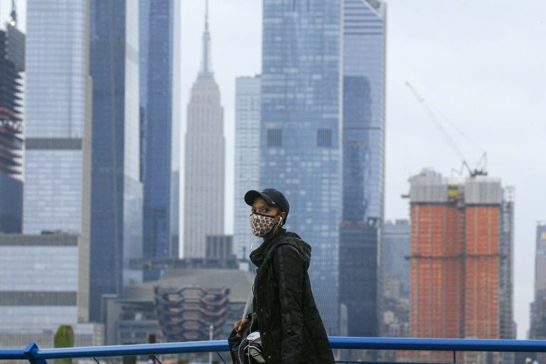 A person wearing a face mask walks in Weehawken, New Jersey, on November 11, 2020, with the New York skyline in the background. Photo: AFP