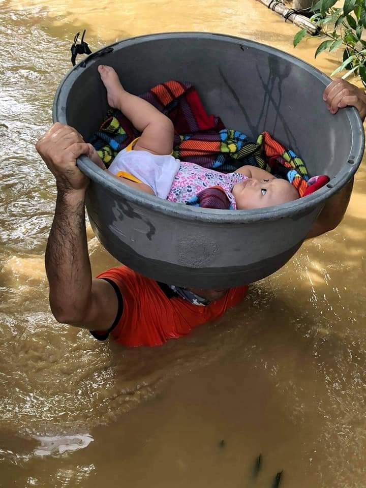 A member of the Philippine Coast Guard carries a baby during a rescue operation, after Typhoon Vamco resulted in severe flooding, in the Cagayan Valley region in northeastern Philippines, November 13, 2020. Picture taken November 13, 2020. Mandatory credit Philippine Coast Guard/Handout via Reuters