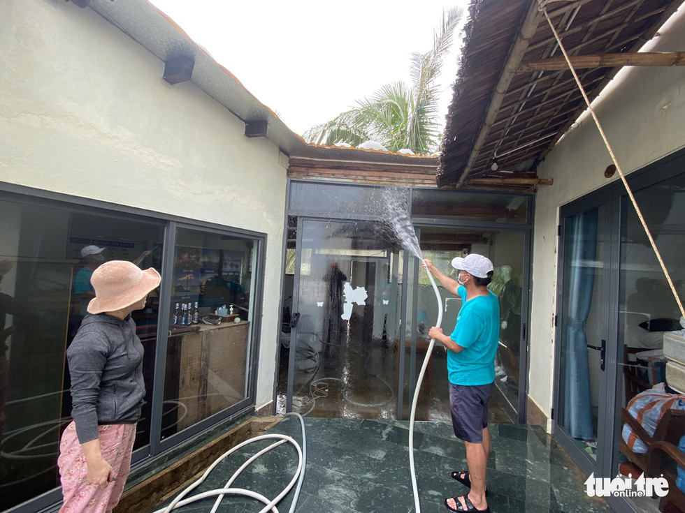 The owner of a lodging facility in Hoi An City is cleaning up his place after Storm Vamco landfall. Photo: Le Trung / Tuoi Tre