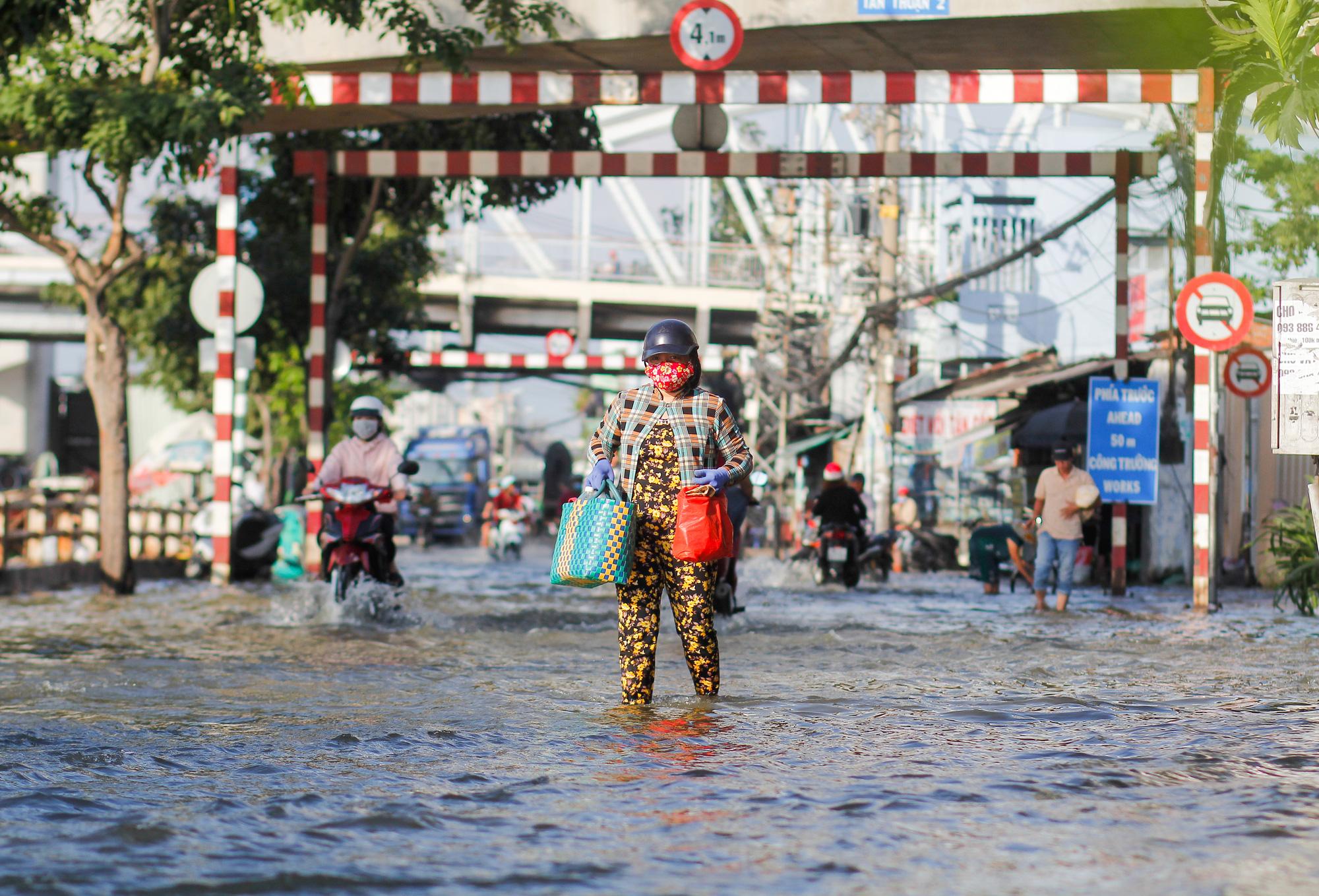 A woman walks on flooded Tran Xuan Soan Street in District 7, Ho Chi Minh City, November 15, 2020. Photo: Chau Tuan / Tuoi Tre