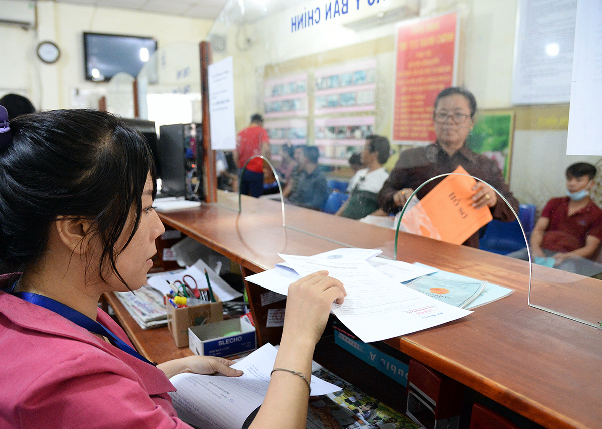 A public servant processes paperwork at a commune-level People's Committee in Binh Chanh District, Ho Chi Minh City. Photo: Minh Anh / Tuoi Tre
