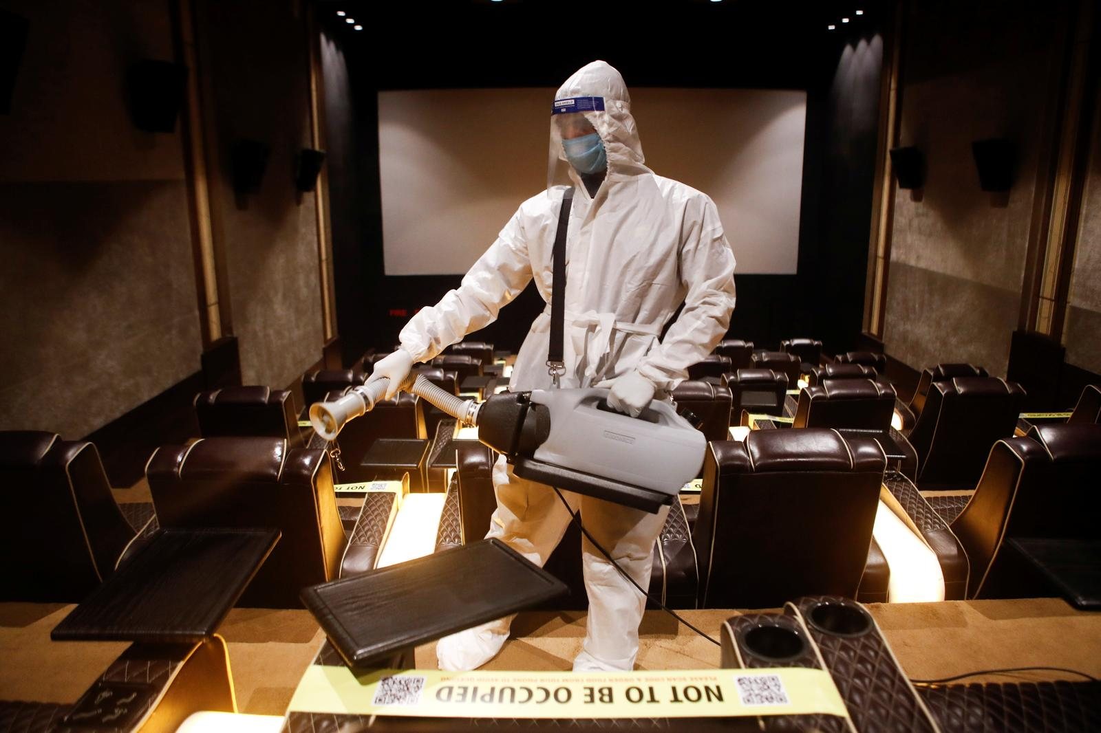 A man in personal protective equipment (PPE) sanitizes a cinema hall before a movie amid the spread of the coronavirus disease (COVID-19) in Mumbai, India November 15, 2020. Photo: Reuters