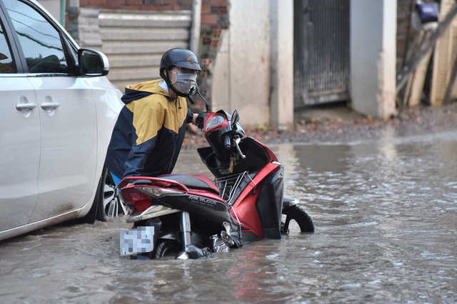 A woman pushes her broken-down motorbike on a flooded street in Ho Chi Minh City, November 16, 2020. Photo: Duyen Phan / Tuoi Tre