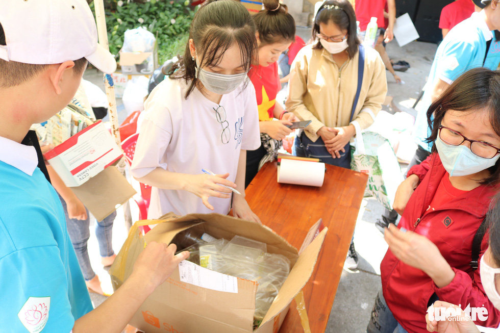 """Volunteers at the social event """"Doi rac lay cay"""" retrieves plastic waste from attendees. Photo: Hoang An / Tuoi Tre"""