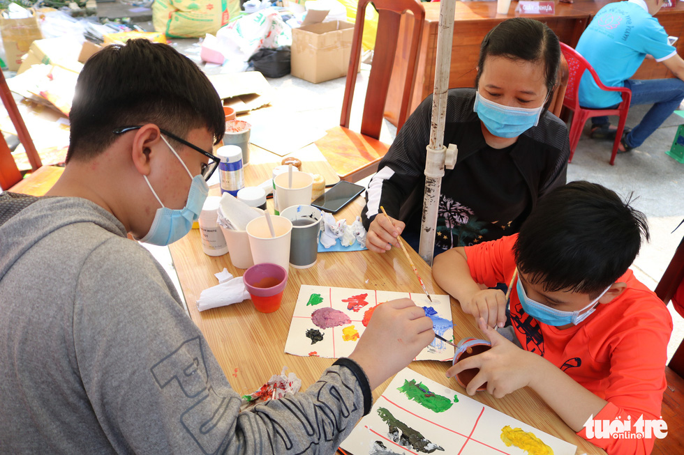"""8-year-old Kien Thien and his family paint a plant pot at the """"Doi rac lay cay"""" event in Ho Chi Minh City. Photo: Hoang An / Tuoi Tre"""