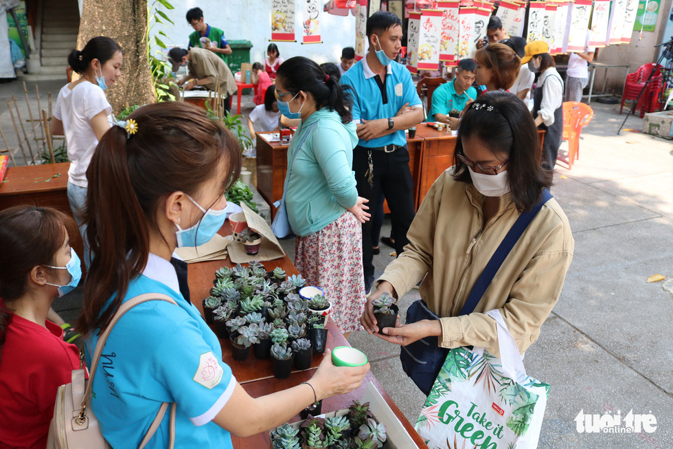 """Event-goers pick their plant as a reward for their plastic waste donation to the """"Doi rac lay cay"""" event. Photo: Hoang An / Tuoi Tre"""