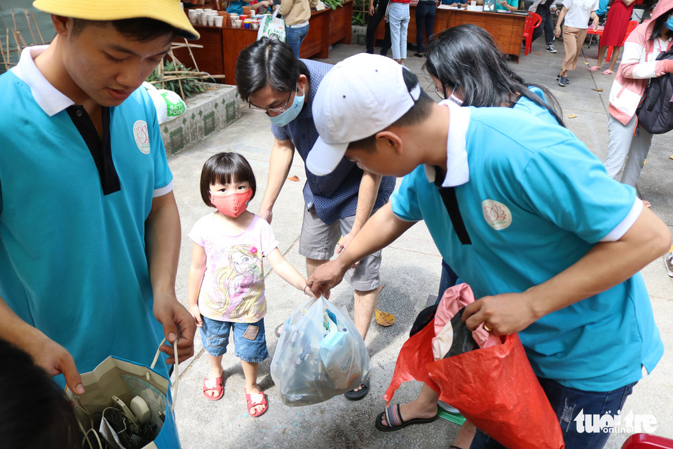 """Event-goers bring discarded milk boxes to donate at the """"Doi rac lay cay"""" event. Photo: Hoang An / Tuoi Tre"""