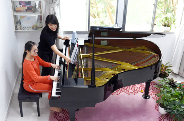 Anh Thu (right) and her tutor Thuy Yen (left) during a piano lesson. Photo: Tuoi Tre