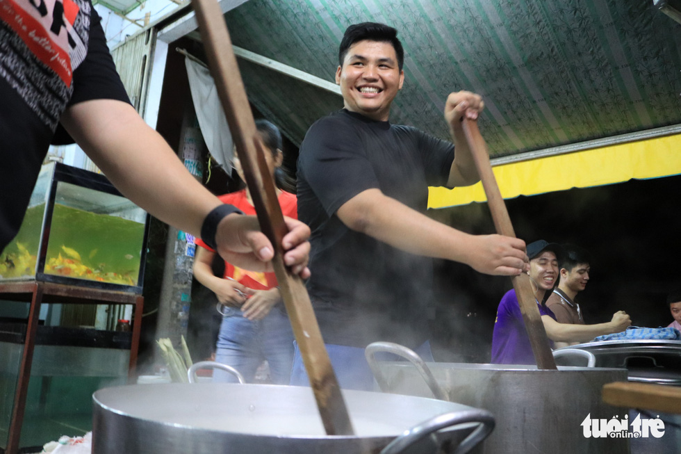 Thanh Bao, a resident in District 11, Ho Chi Minh City, Vietnam stirs the porridge in one of the group's four large pots. Each member takes turnings stirring the pots to make sure the meals comes out perfectly