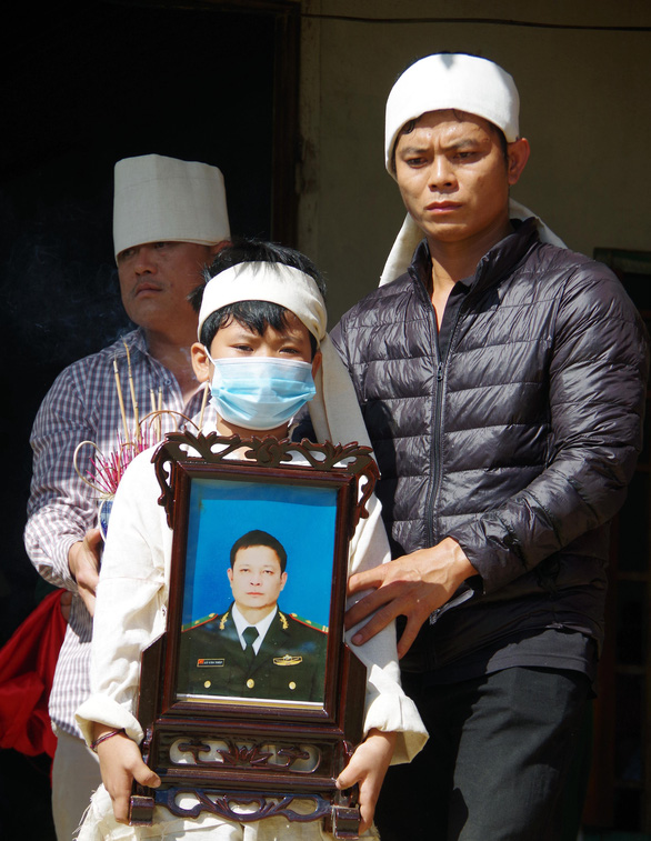A son of Lo Van Thep carries his father's photo during the funeral held on November 18, 2020 in Bum Nua Commune, Muong Te District, Lai Chau Province. Photo: Đ.D. / Tuoi Tre