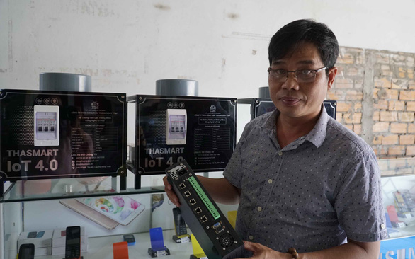 Ngo Hung Thang is seen holding SmartViet HT-8917, his first irrigation system blueprint. Photo: Ngoc Tai / Tuoi Tre