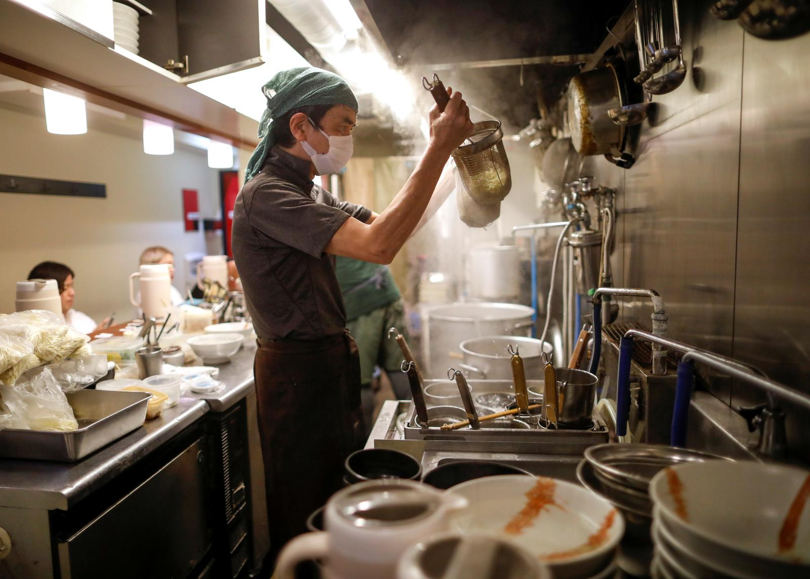 Sixty-year-old Yashiro Haga cooks ramen noodles at his noodle shop 'Shirohachi', amid the coronavirus disease (COVID-19) outbreak, in Tokyo, Japan November 20, 2020. Photo: Reuters