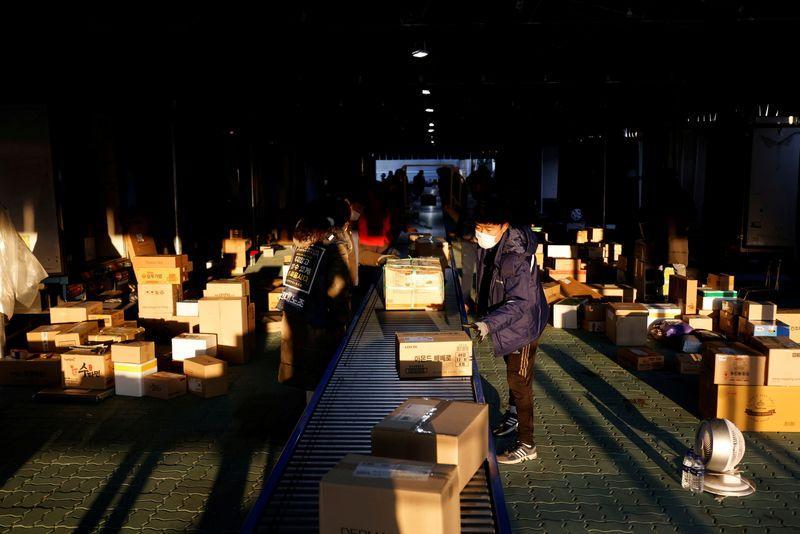 Parcel delivery workers sort parcels at a Hanjin Transportation distribution centre in Gwangju, South Korea, November 10, 2020. Photo: Reuters