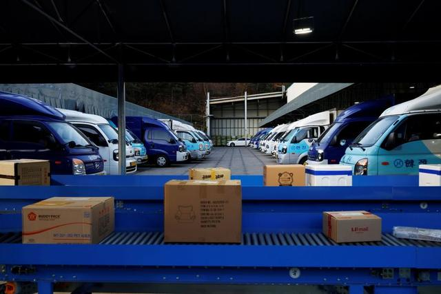 Parcels are seen on conveyor belts near delivery trucks parked at a Hanjin Transportation distribution centre in Gwangju, South Korea, November 10, 2020. Photo: Reuters