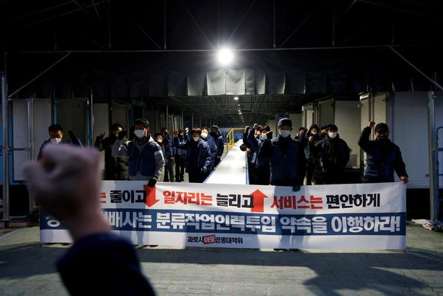 Parcels delivery workers chant slogans at a Hanjin Transportation distribution centre in Gwangju, South Korea, November 10, 2020. Banner reads 'Reduce overwork, increase jobs, for high quality service'. Photo: Reuters
