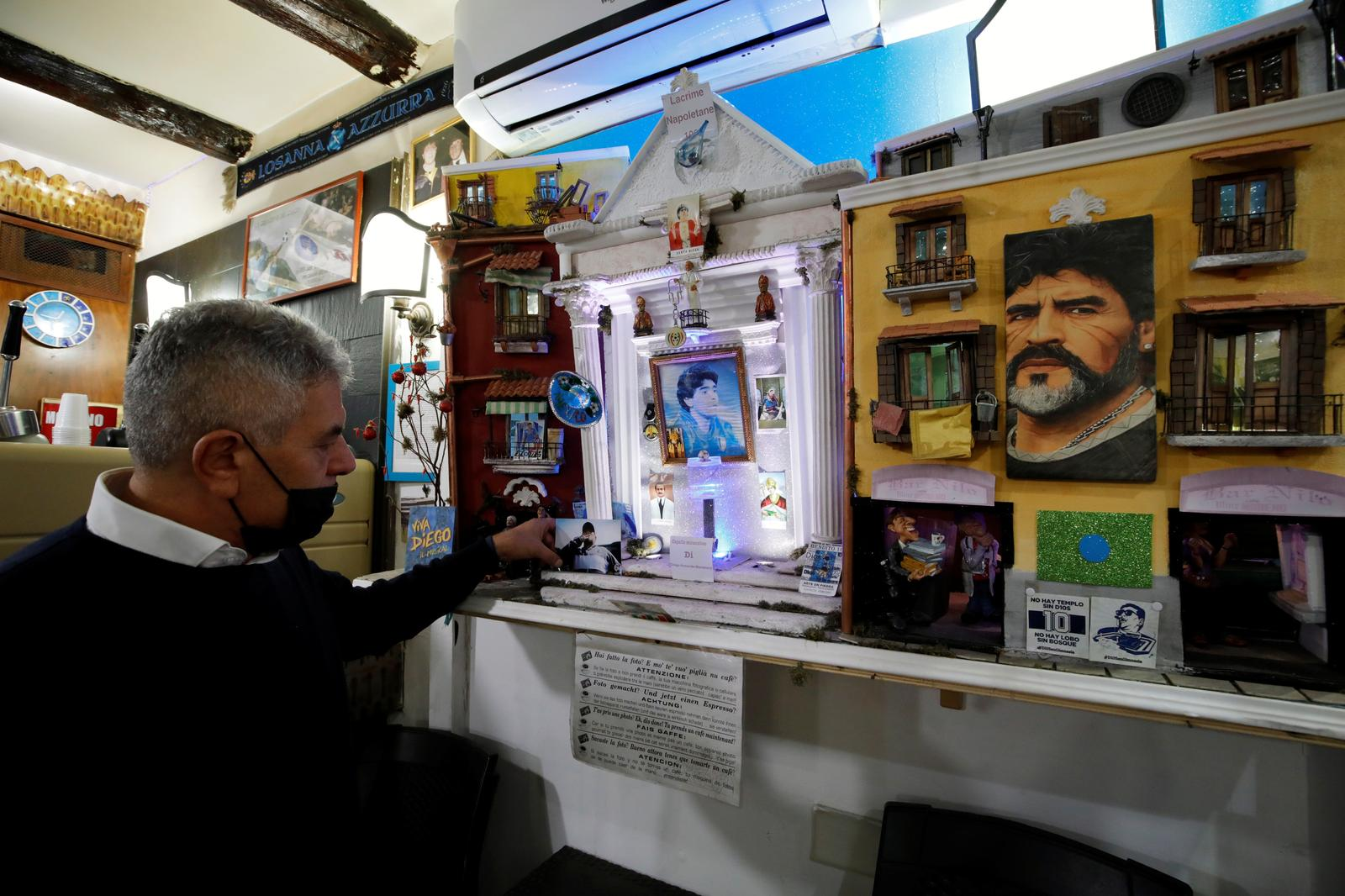 A man wearing a protective face mask holds a picture as he mourns the death of Argentine soccer legend Diego Maradona, in Naples, Italy, November 26, 2020. Photo: Reuters