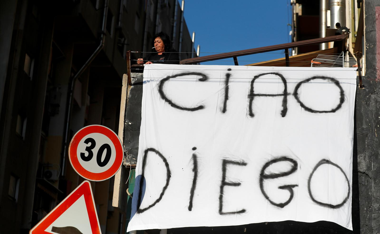 A woman hangs out on a balcony a sheet reading 'Bye Diego' to mourn the death of Argentine soccer legend Diego Maradona, in Naples, Italy November 26, 2020. Photo: Reuters