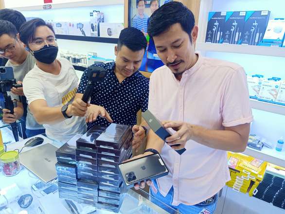 Vietnamese actor Huy Khanh (right) unboxes his new iPhone 12 at Minh Tuan Mobile store in Ho Chi Minh City, November 27, 2020. Photo: Duc Thien / Tuoi Tre