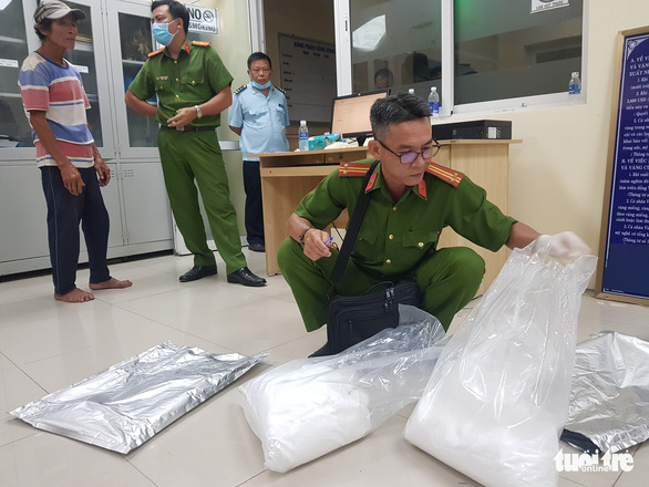 A policeman examines the evidences at the police station in Tinh Bien District, An Giang Province, November 26, 2020. Photo: Buu Dau / Tuoi Tre
