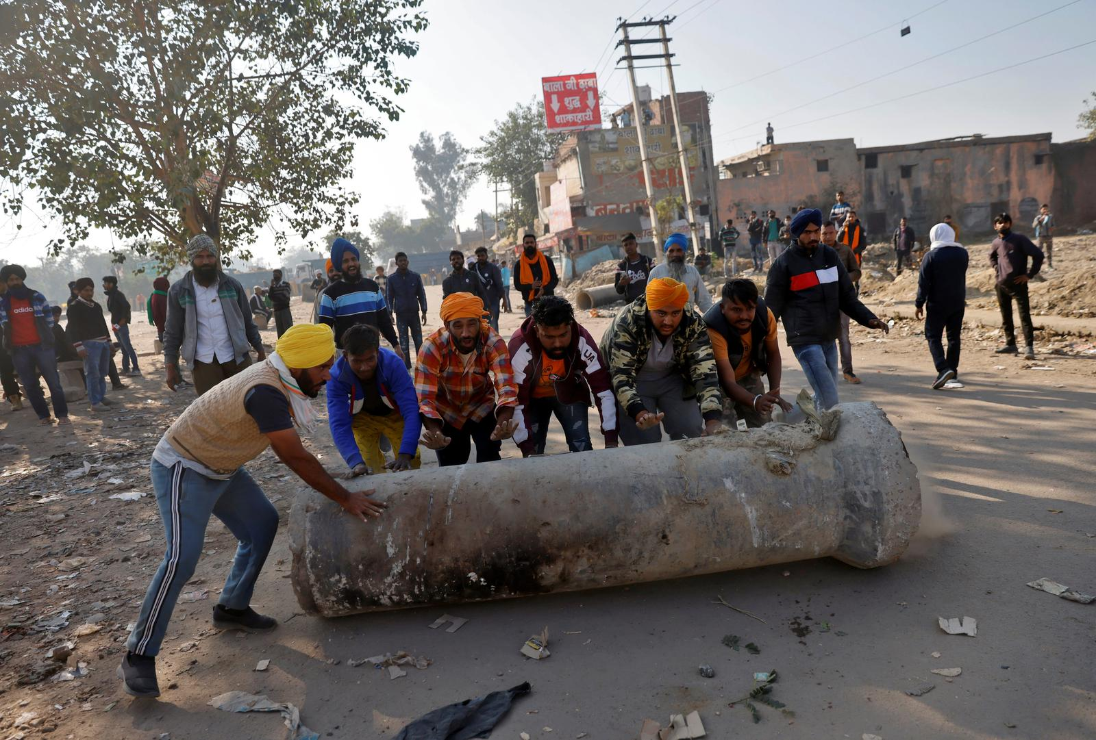 Farmers push a cement pipe to use it as a roadblock during a protest against the newly passed farm bills at Singhu border near Delhi, India, November 28, 2020. Photo: Reuters