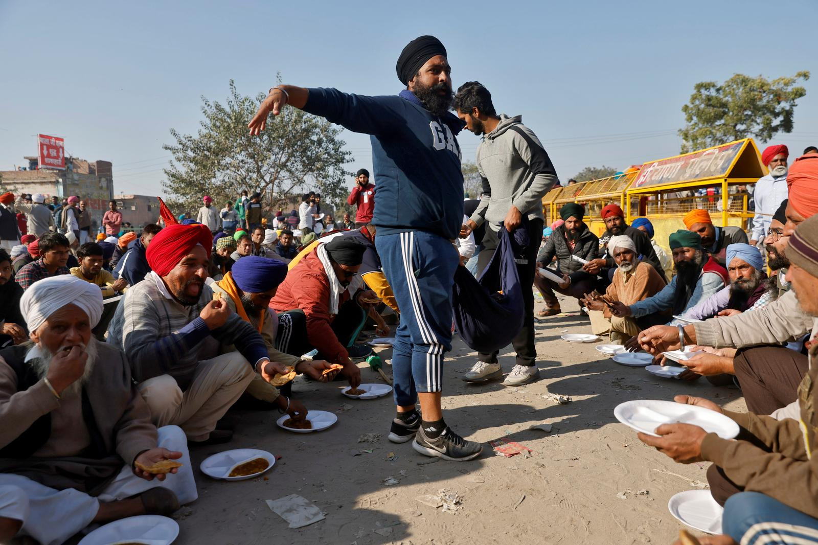 Farmers have their meal at a site of a protest against the newly passed farm bills at Singhu border near Delhi, India, November 28, 2020. Photo: Reuters